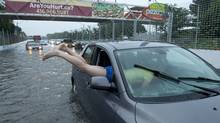 A woman gets gets back in her car in flood water on Lakeshore West during a storm in Toronto on Monday, July 8, 2013. (Frank Gunn/THE CANADIAN PRESS)
