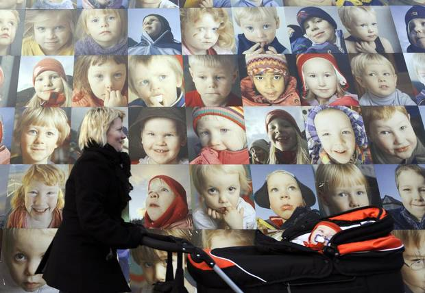 A mother pushes a stroller by a wall with portraits of children on October 8, 2008, in Reykjavik, Iceland.