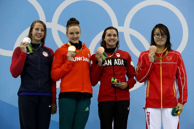 Silver medalist Kathleen Baker of the United States, gold medal medalist Katinka Hosszu of Hungary and bronze medalist's Kylie Masse of Canada and Yuanhui Fu of China pose on the podium during the medal ceremony for the Women's 100m Backstroke Final on Day 3 of the Rio 2016 Olympic Games at the Olympic Aquatics Stadium on August 8, 2016 in Rio de Janeiro, Brazil.