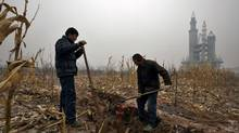Farmers dig a water well in a field that includes an abandoned building that was to be part of an amusement park called 'Wonderland', on the outskirts of Beijing on Dec. 5, 2011. Construction work at the park, which was promoted by developers as 'the largest amusement park in Asia', stopped around 1998 after funds were withdrawn due to disagreements over property prices with the local government and farmers. Local governments are often dependent on land sales to fund payments on a staggering 10.7 trillion yuan ($1.7-trillion) of debt. (DAVID GRAY/DAVID GRAY/REUTERS)