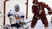 New York Islanders goalie Evgeni Nabokov, left, blocks the puck as Phoenix Coyotes' Shane Doan looks on during the second period of an NHL hockey game on Saturday, Jan. 7, 2012, in Glendale, Ariz. The Coyotes won 5-1. (AP Photo/The Arizona Republic, Emmanuel Lozano ) (Emmanuel Lozano/AP)