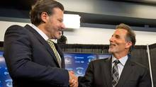 Vancouver Canucks co-owner Francesco Aquilini, left, greets new head coach John Tortorella during a news conference announcing Tortorella's hiring on June 25, 2013. (Darryl Dyck/The Canadian Press)