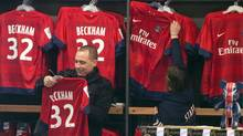 A man looks at a PSG soccer shirt on display with the name of British soccer player David Beckham, at the the Club's shop on the Champs Elysees, in Paris, Friday, Feb. 1, 2013. (Associated Press)