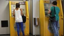 Two women withdraw money from an ATM at a branch of Spain's La Caixa bank in Mataro on September 4, 2012. (GUSTAU NACARINO/REUTERS)
