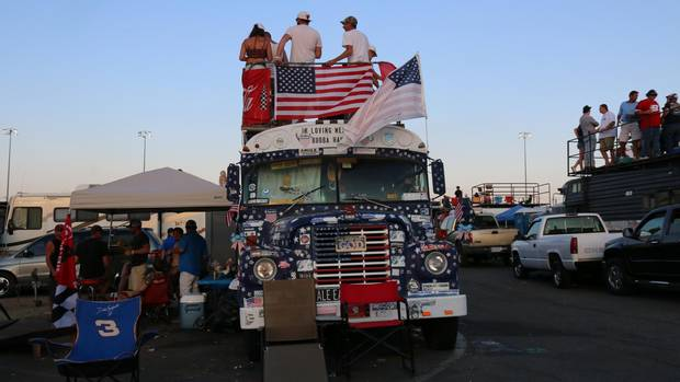 Fans atop a school bus take in the racing as the sun sets during the Coca-Cola 600 at Charlotte Motor Speedway.