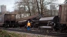 An inspector looks over CP train cars that flipped over after derailing in the Vancouver suburb of Burnaby, B.C., on Jan. 11, 2014. (Ben Nelms for The Globe and Mail)