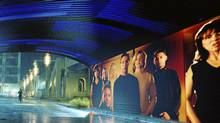 "Tom Cruise runs a gantlet of electronic billboards that scan his retinas and hurl personalized pitches his way in a scene from Spielberg's new movie ""Minority Report."" Many of the film's futuristic visions, including a holographic greeter at the Gap and animated cereal boxes, could become real using technology being developed today. (20th Century Fox)"