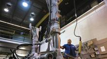 A worker works at on Landing gear without wheels at the Heroux Devtek plant in Quebec. (Handout)
