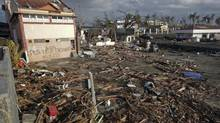 A man searches through debris in front of a house with a message asking for help in a part of Tacloban devastated by Typhoon Haiyan November 16, 2013. (JOHN JAVELLANA/REUTERS)