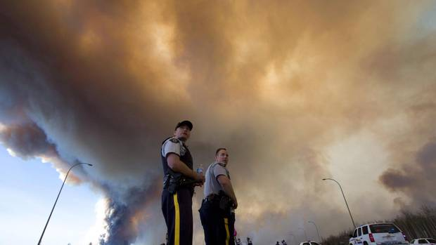 Police officers direct traffic under a cloud of smoke from a wildfire in Fort McMurray, Alta., on May 6, 2016.