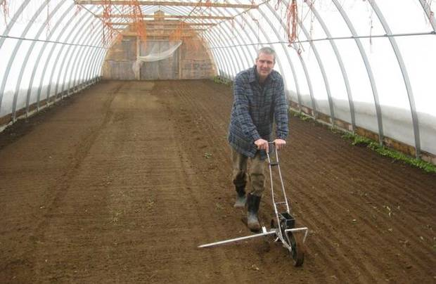 Brent Preston uses his old Jang to plant seeds in the greenhouse.