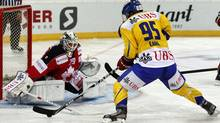 Team Canada's goalkeeper Jake Allen tries to defend as Robbie Earl of HC Davos shoots to score a goal during their game at the Spengler Cup. (ARND WIEGMANN/Reuters)