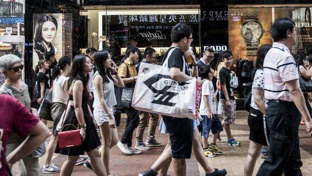 Shoppers and pedestrians walk past a Rado Watch Co. store on Russell Street in the Causeway Bay shopping district of Hong Kong, China, on Sunday, Aug. 9, 2015.