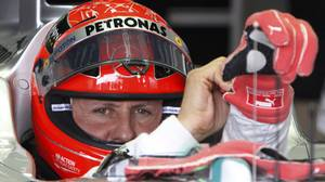 Michael Schumacher of Germany puts on his gloves as he sits in his car during the third practice session of the Japanese F1 Grand Prix at the Suzuka circuit October 6, 2012.