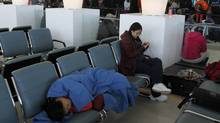 A passenger sleeps on a bench as long delays affect Toronto's Pearson Airport due the extreme cold on Jan. 7, 2014. (FERNANDO MORALES/THE GLOBE AND MAIL)
