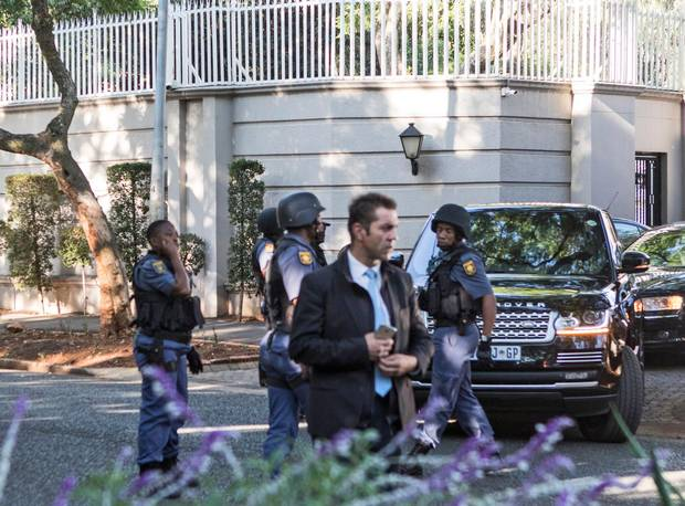 South African police officers stand guard at the Gupta family compound in Johannesburg on February 14.