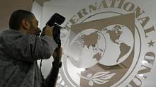 A photographer takes pictures through a glass carrying the International Monetary Fund (IMF) logo during a news conference in Bucharest March 25, 2009. (© Bogdan Cristel / Reuters/REUTERS)
