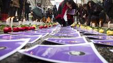 Photos and roses are place on the ground as part of a memorial to missing women in Vancouver on Dec. 17, 2012. (JOHN LEHMANN/THE GLOBE AND MAIL)