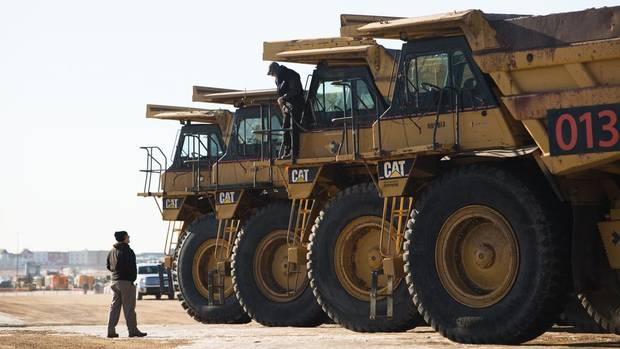 Potential buyers check out haul trucks during an auction at Ritchie Bros. in Nisku, Alberta on Thursday, February 25, 2016. Amber Bracken for The Globe and Mail