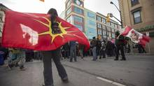 A native protester from the Idle No More movement holds a warrior flag during a flash mob round dance demonstration blocking an intersection in downtown London, Ontario, Thursday, January 10, 2013. (Geoff Robins/Canadian Press)