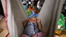 """The next great milestone we must achieve in the story of AIDS is ending mother-to-child transmission,"""" HIV-positive Ei Ei Phyu, who lives at the hospice with his HIV-positive mother, sleeps in a hammock at the HIV/AIDS hospice founded by a member of the National League for Democracy (NLD) party in the suburbs of Yangon May 26, 2012. Their plight demonstrates the painful limits of democracy in Myanmar. While the government is pursuing reforms that promise to overhaul its health ministry and other institutions, the process is too slow to bring change to its most destitute. There are few better examples than AIDS sufferers, who due to a combination of poor education, social stigma and bureaucratic mismanagement are isolated in clinics, cut off from society. (Damir Sagolj/Reuters)"""