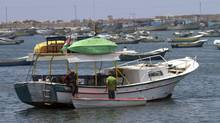 Palestinian fishermen prepare their boat ahead of the expected arrival of a flotilla of hundreds of pro-Palestinian activists trying to sail into the Gaza Strip, in Gaza city, Friday, May 28, 2010. (Adel Hana/The Associated Press/Adel Hana/The Associated Press)