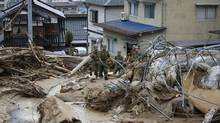 Japan Self-Defense Force (JSDF) soldiers search for survivors as a site where a landslide swept through a residential area at Asaminami ward in Hiroshima, western Japan, August 20, 2014. (Toru Hanai/REUTERS)