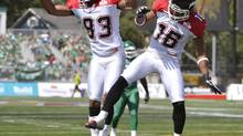 Calgary Stampeders' Romby Bryant (L) celebrates his touchdown against the Saskatchewan Roughriders with team mate Marquay McDaniel during the first half of their CFL game in Regina August 25, 2012. (FRED GREENSLADE/REUTERS)
