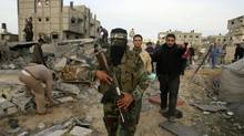 A Palestinian Hamas militant walks in the rubble of the destroyed house of Hamas militant Mohammad Abu Shmala, following an Israeli air strike in Rafah, southern Gaza Strip, Friday, Nov. 16, 2012. (Eyad Baba/AP Photo)