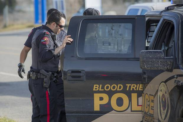Constable Rayan Najjar with the Blood Tribe Police Service in Stand Off, Alta., detains a local resident who was suspected of carrying a firearm.