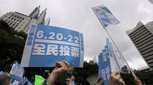 """Pro-democracy supporters raise banners that read """"referendum"""" during a kickoff ceremony of an referendum on democracy in Hong Kong on June 20, 2014. (VINCENT YU/ASSOCIATED PRESS)"""