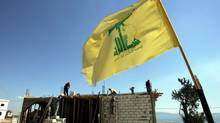 In front of a Hezbollah flag, Syrian workers rebuild a damaged house in July, 2007, that was destroyed during the previous summer's conflict between Israel and Hezbollah at the Lebanese village of Maroun el-Ras. (HUSSEIN MALLA/ASSOCIATED PRESS)