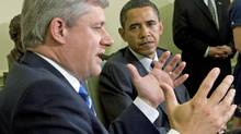 U.S. President Barack Obama looks on as Prime Minister Stephen Harper speaks to reporters in the Oval Office on Sept. 16, 2009. (Adrian Wyld/The Canadian Press)