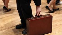 A man grabs his briefcase as he waits in line to speak with employers at the UJA-Federation Connect to Care job fair in New York, March 21, 2012. (SHANNON STAPLETON/Reuters)