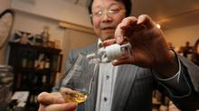 Hideo Yamaoka pours the last drop from a rare 1910 Ainslie's whisky. Mr. Yamaoka keeps a second apartment in downtown Tokyo apartment to hold his 2,000-bottle whisky collection. (Nathan VanderKlippe/The Globe and Mail)
