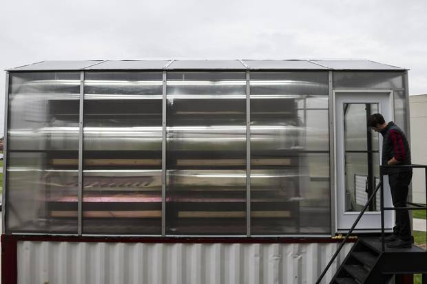 The ground floor is filled with a large fish tank, along with a system of pumps and filters that provide nutrient-rich water to the greenhouse set atop the shipping container.