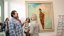 "Artist and filmmaker Julian Schnabel talks with visitors to his show ""Julian Schnabel: Art and Film"" at the Art Gallery of Ontario in Toronto. (Della Rollins/The Globe and Mail)"