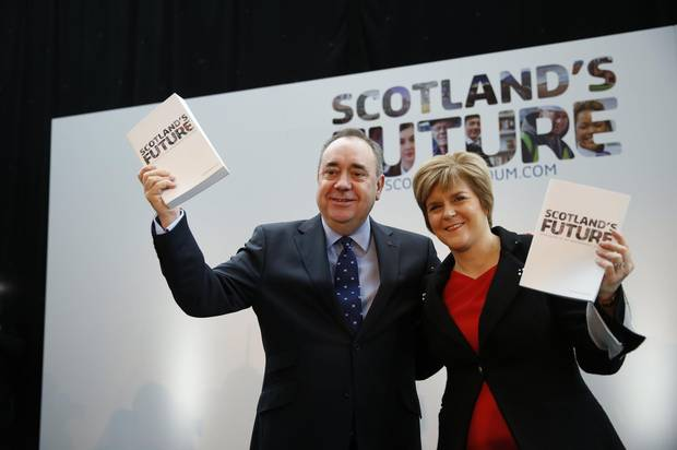 A 2013 photo shows Scotland's First Minister Alex Salmond and deputy First Minister Nicola Sturgeon holding copies of the referendum white paper on independence during its launch in Glasgow, Scotland.