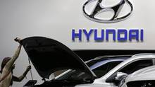 A visitor looks at a Hyundai car at the Paris Mondial de l'Automobile Sept. 28, 2012. Both Hyundai and Kia have admitted to overstating the fuel economy ratings of some of their vehicles. (CHRISTIAN HARTMANN/REUTERS)