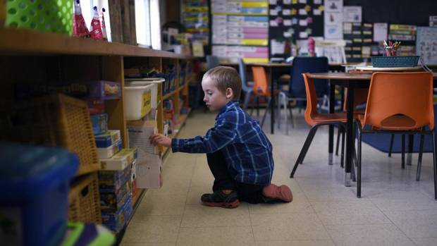 Cameron Taylor, 6, completes his school work as he poses for a photo in his classroom at Mineola Public School in Mississauga on December 21, 2016. He is one of only two Grade 1 English-track students at the school. The rest of his Grade 1, 2, 3 split class is in French immersion.
