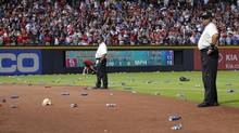 Atlanta Braves officials pick up trash on the field as security stand by during the eighth inning of the National League wild card playoff game against the St. Louis Cardinals, Friday, Oct. 5, 2012, in Atlanta. The Cardinals won baseball's first wild-card playoff, taking advantage of a disputed infield fly call that led to a protest and fans littering the field with debris to defeat the Braves 6-3. (Todd Kirkland/AP)
