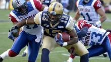 Winnipeg Blue Bombers' Chris Matthews (C) is tackled by Montreal Alouettes' Billy Parker (L) and Seth Williams during the first half of their CFL football game in Winnipeg, November 3, 2012. (FRED GREENSLADE/REUTERS)