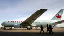 An Air Canada flight crew walks past an aircraft in Montreal. (Christinne Muschi/Reuters)