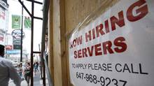 Pedestrians and shoppers walk past Now Hiring sign in Toronto. (Deborah Baic/The Globe and Mail)