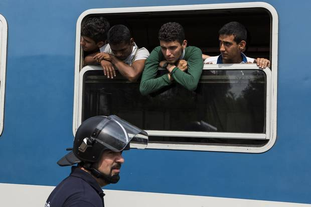 Syrian refugee Khaled Allak leans out of a train window on Sept. 3, 2015 while en route from Budapest, Hungary to a refugee camp in Bicske. After learning the train was not going to Germany as hoped, Mr. Allak and other young Syrians escaped from the train and trekked over land to Germany.