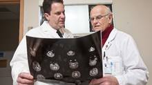 Dr. Paul Echlin and Dr. Charles Tator, both experts in concussions, are seen with MRI brain scans at Toronto Western Hospital on February 6, 2011. (JENNIFER ROBERTS/THE GLOBE AND MAIL)