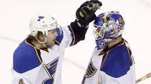 St. Louis Blues goalie Brian Elliott (1) is congratulated by defenseman Kris Russell (4) after defeating the San Jose Sharks in Game 4 of their NHL Western Conference quarter-final playoff hockey game in San Jose, California April 19, 2012. (ROBERT GALBRAITH)