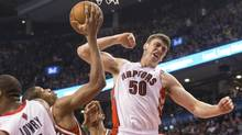 Toronto Raptors' Tyler Hansbrough (right) celebrates scoring on a rebound in front of Milwaukee Bucks' Giannis Antetokounmpo (centre) during first half NBA basketball action in Toronto on Monday, April 14, 2014. (Chris Young/THE CANADIAN PRESS)