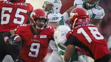 Calgary Stampeders' Jon Cornish, left, runs the ball during first half CFL action against the Saskatchewan Roughriders in Calgary, Alta., Saturday, Oct. 26, 2013. (Jeff McIntosh/THE CANADIAN PRESS)
