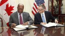 U.S. Trade Representative Ron Kirk, left, and International Trade Minister Ed Fast sign the Softwood Lumber Extension Agreement in Washington on Jan. 23, 2012. The deal limits Canadian duty-free exports to the U.S. market. (KEVIN LAMARQUE/KEVIN LAMARQUE/REUTERS)